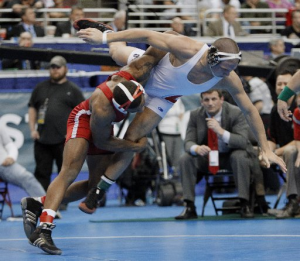An image of Jordan Burroughs in college finishing a double leg takedown against an opponent in a white singlet.  He has his opponent lifted off the mat as he's driving through.
