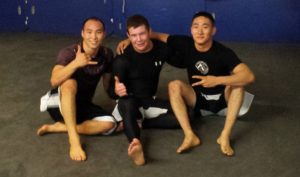 A picture of Dickie White sitting between 2 other guys after doing some Jiu-Jitsu at Ironworks Gym in Binghamton, NY.