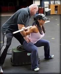 Strength Training For Wrestling using Box Squats- an image of Dave Tate working with a female client on Box Squat technique