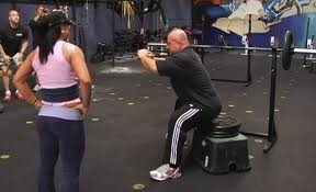 An image of Dave Tate demonstrating/teaching a Box Squat at a seminar