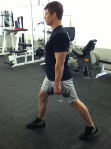 An image of Dickie White at the start of a Split Squat holding 2 light dumbbells.