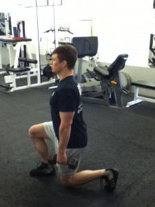 An image of Dickie White at the bottom of a Split Squat with his trail knee touching the ground. He's holding 2 light dumbbells, one in each hand.