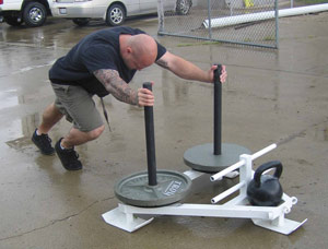 wrestling conditioning post- an image of Jim Wendler pushing the high bars on a Prowler in a parking lot.