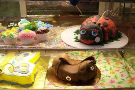 A picture of 4 cakes including one that looks like a ladybug and one that looks like a bunny.