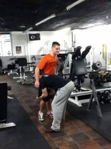 A picture of Dickie White on a single leg of a gym member. His hips are driven far back and are not under him.