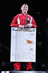 A picture of Kyle Dake holding his winning bracket while standing on top of the podium at the NCAA tournament.