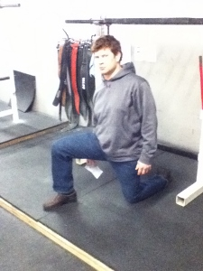 A picture of Dickie White in a kneeling staggered stance displaying a hip flexor stretch.