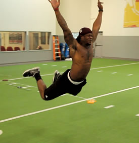 A shirtless athlete performing a horizontal jump on an indoor turf field.