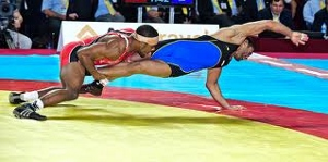 Jordan Burroughs shooting an explosive double leg near the edge of the mat in a Freestyle match.