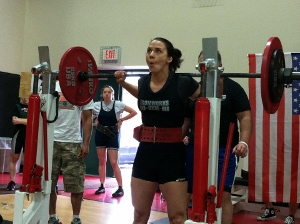 A picture of Laura Monroe squatting in a powerlifting competition.
