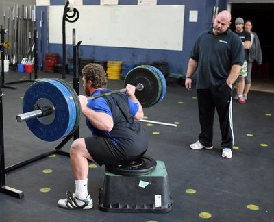An image of Dave Tate teaching someone to Box Squat. The squatter is sitting on a box with 315 on the bar and Dave is watching from the side.