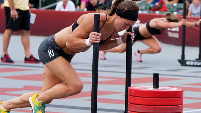 An image of a very in shape woman (at the CrossFit Games) pushing a heavy sled with red plates stacked up in the middle.