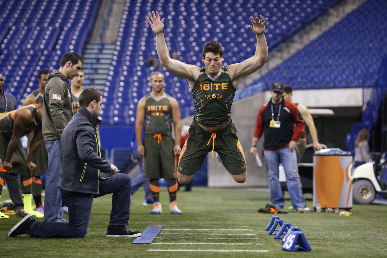 "An image of an athlete in a green tank top and shorts mid-jump during a Broad Jump test. There are other athletes waiting in line and a ""tester"" kneeling on the left side of the picture. This athlete is jumping on turf."