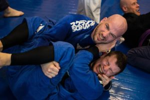 A picture of Dickie White and Dennis Sugrue in blue gis doing jiu-jitsu.