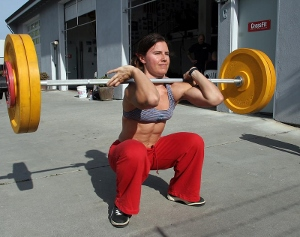 A picture of a fit woman performing a front squat outside of a gym on pavement. She is in the bottom position of the front squat and is wearing red pants.