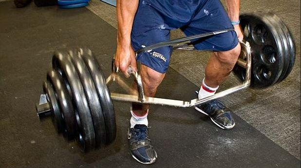 This shows a trap bar deadlift in progress. The photo is focused on the lifter's lower body so only his legs and the trap bar are shown.